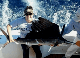 Young lady and family releases her first Atlantic Sailfish on a vacation charter while staying in Kill Devil Hills NC.