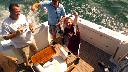 Anglers young and old enjoy showing off their catch while standing on our deck during a Nags Head vacation charter trip.