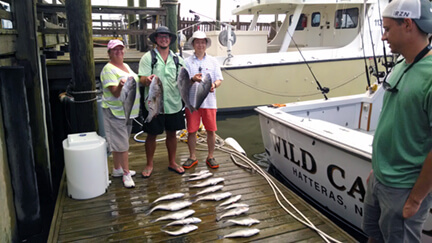 Family group staying in Nags Head NC posing with fish caught on a half day Oregon Inlet charter.