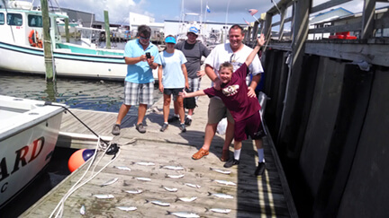 Family group staying in Duck NC standing with their catch of Spanish mackerel and bluefish.